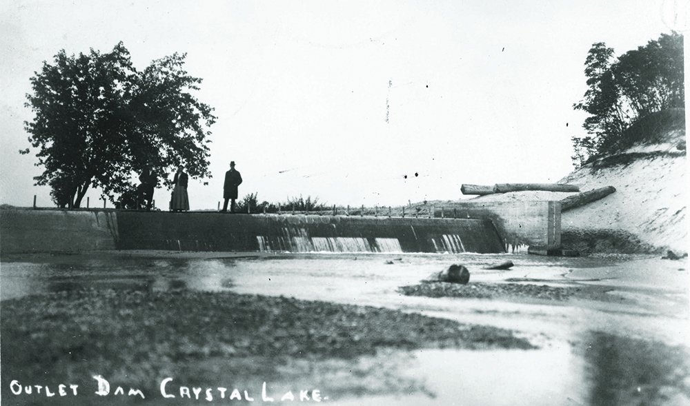 "Crystal Lake Outlet Dam (ca. 1912-1913).  Archives of the Traverse City History Center, Image 52, entitled, ""Crystal Lake outlet dam with three people standing in (sic) the lake"".   Photo courtesy of the History Center of Traverse City."