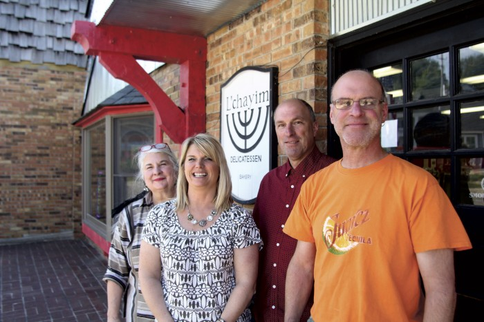 Sally Berlin (far left) of Crystal Crate & Cargo, Kitty Ely of Northern Decor, and Jonathan Clark (far right) of L'Chayim all participate in Hometown Giving, a project created by Cameron Clark (middle). Photo by Aubrey Ann Parker.