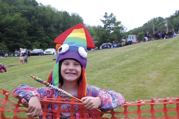 "Audrey Gollan takes a break from ""sledding"" down the Elberta hill on cardboard to eat some candy at the Elberta Solstice Festival. Photo by Aubrey Ann Parker."
